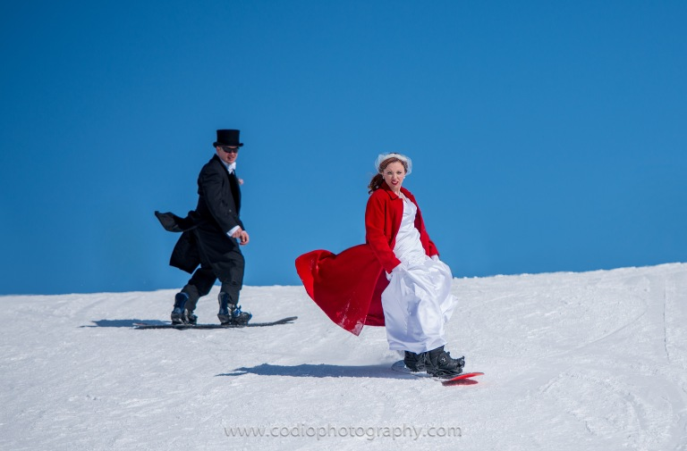 husband and wife snowboarding in wedding clothes